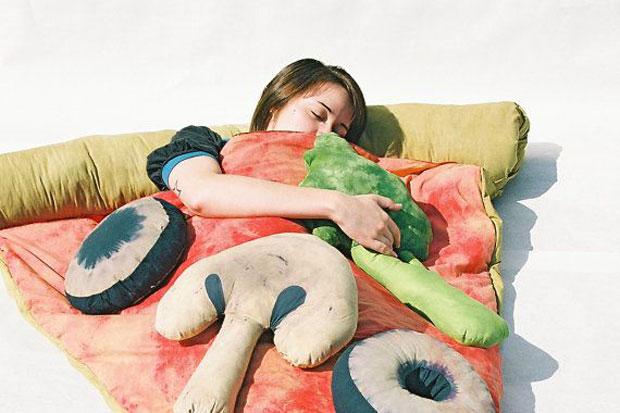 Girl having the best rest of her life in this amazing pizza bed
