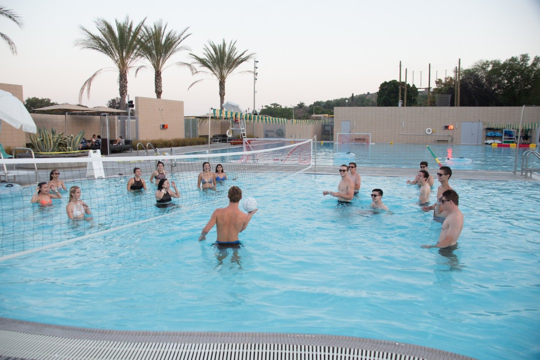 Students playing volleyball in pool