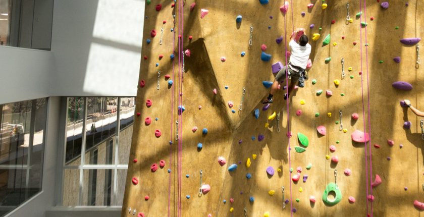 Two students climb the rock wall in the BRIC.