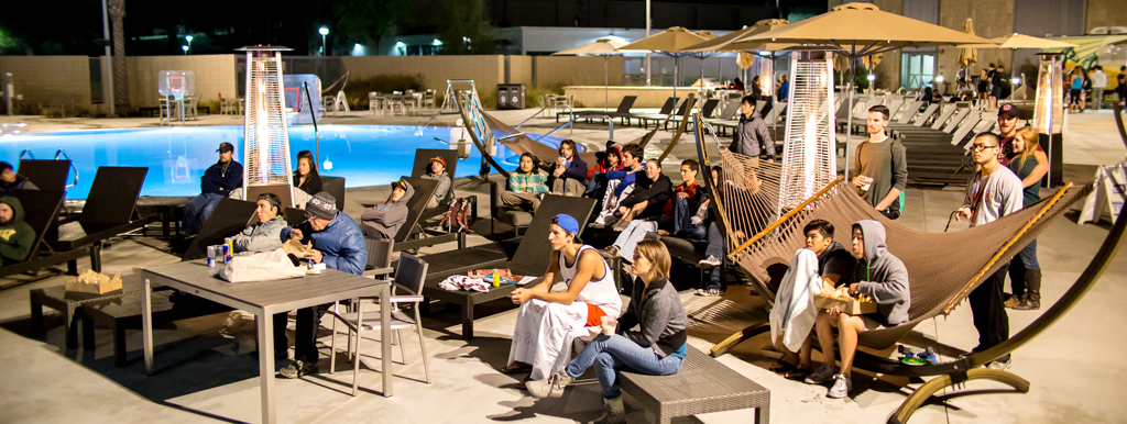 Students watching a movie at the pool deck at night