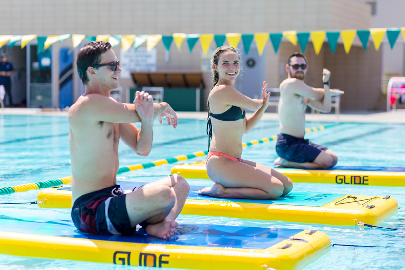 Three students stretching on FitFloats in the pool