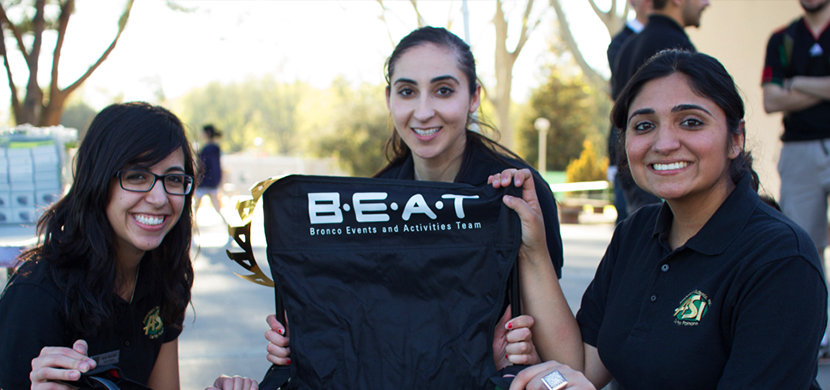 Three women holding up a BEAT t-shirt and smiling for the camera