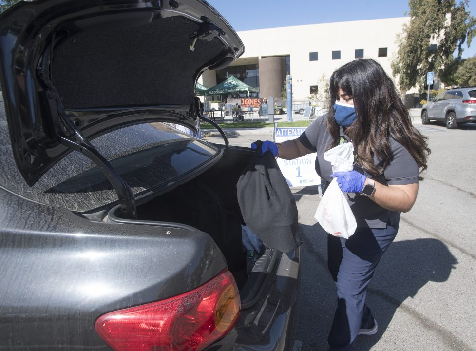 Woman loading groceries into trunk