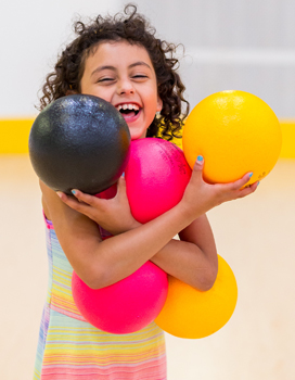 Children laughing while holding five dodge balls
