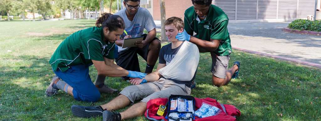 Three staff members medically assisting a student