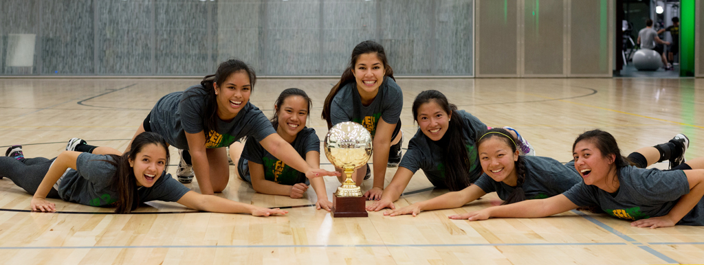 Women's Volleyball team posing with their championship trophy
