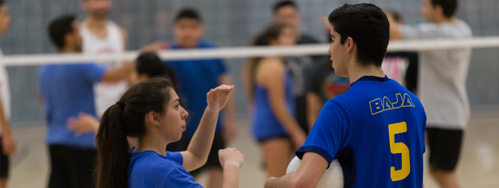 Two students talking at a Intramurals volleyball game