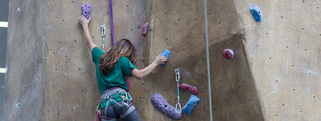 Female student climbing the rock wall