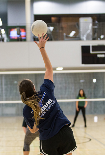Student serving a volleyball