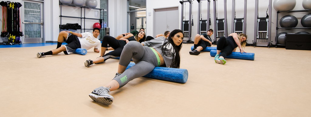 Students using foam rollers in a studio class