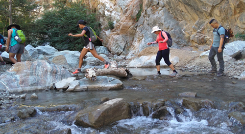 Individuals crossing a stream on an outdoor hike