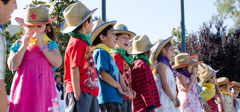 group of children dressed up with cowboy hats and scarves