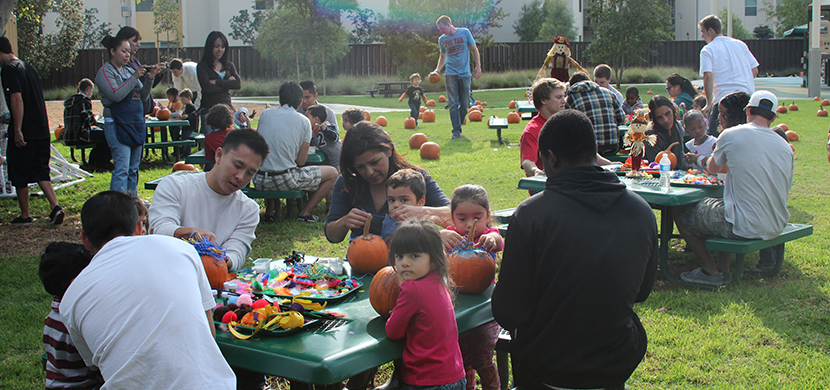 Children and parents decorating pumpkins for Halloween