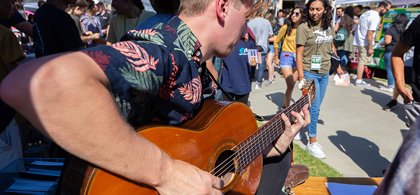 A student playing the guitar during a school fair