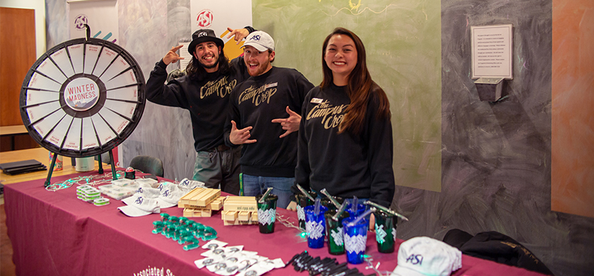 Three students smiling at the camera behind an ASI merchandise table