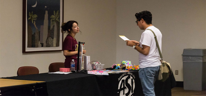 Student talking with another student at a tabling event