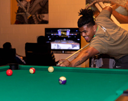 Student playing billiards at the Games Room